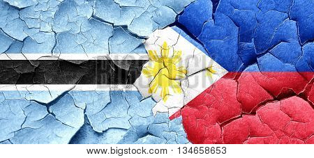 Botswana flag with Philippines flag on a grunge cracked wall