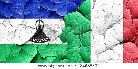 Lesotho flag with Italy flag on a grunge cracked wall