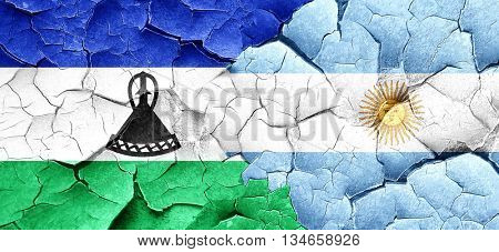 Lesotho flag with Argentine flag on a grunge cracked wall