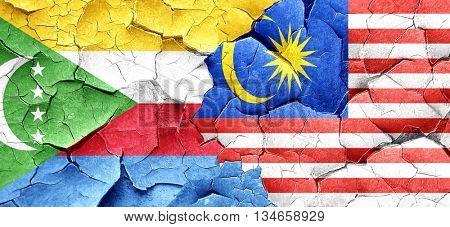Comoros flag with Malaysia flag on a grunge cracked wall