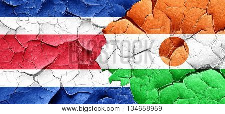 Costa Rica flag with Niger flag on a grunge cracked wall