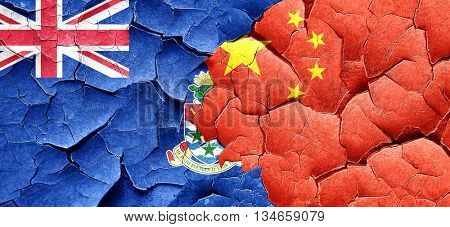 cayman islands flag with China flag on a grunge cracked wall
