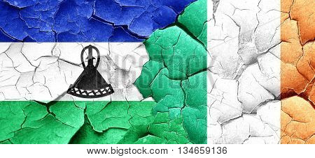 Lesotho flag with Ireland flag on a grunge cracked wall