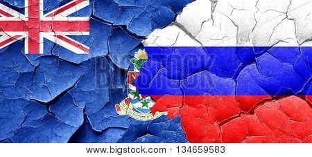 cayman islands flag with Russia flag on a grunge cracked wall