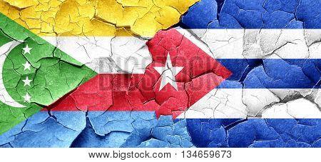 Comoros flag with cuba flag on a grunge cracked wall