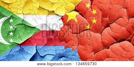 Comoros flag with China flag on a grunge cracked wall