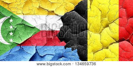 Comoros flag with Belgium flag on a grunge cracked wall