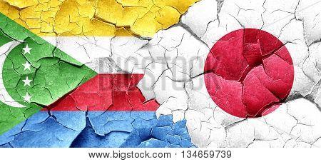 Comoros flag with Japan flag on a grunge cracked wall