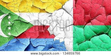 Comoros flag with Madagascar flag on a grunge cracked wall