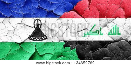 Lesotho flag with Iraq flag on a grunge cracked wall