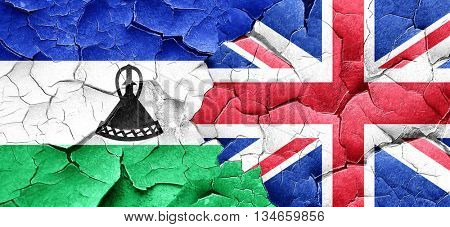 Lesotho flag with Great Britain flag on a grunge cracked wall