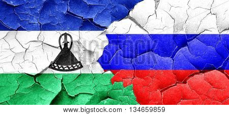 Lesotho flag with Russia flag on a grunge cracked wall