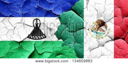 Lesotho flag with Mexico flag on a grunge cracked wall