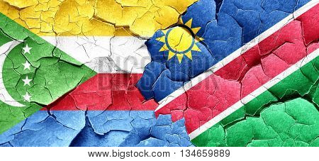 Comoros flag with Namibia flag on a grunge cracked wall