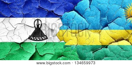 Lesotho flag with rwanda flag on a grunge cracked wall