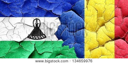 Lesotho flag with Romania flag on a grunge cracked wall