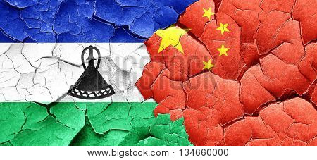 Lesotho flag with China flag on a grunge cracked wall