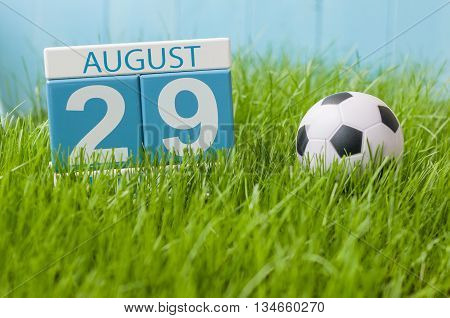 August 29th. Image of august 29 wooden color calendar on green grass lawn background with soccer ball. Summer day. Empty space for text.
