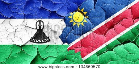 Lesotho flag with Namibia flag on a grunge cracked wall