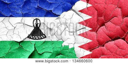 Lesotho flag with Bahrain flag on a grunge cracked wall