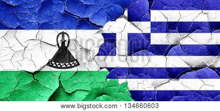 Lesotho flag with Greece flag on a grunge cracked wall
