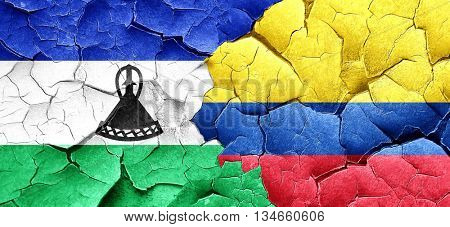 Lesotho flag with Colombia flag on a grunge cracked wall