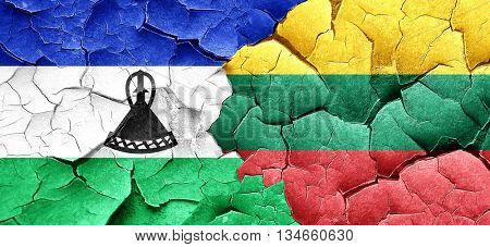Lesotho flag with Lithuania flag on a grunge cracked wall