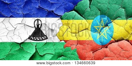 Lesotho flag with Ethiopia flag on a grunge cracked wall