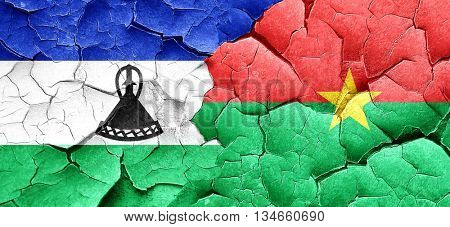 Lesotho flag with Burkina Faso flag on a grunge cracked wall