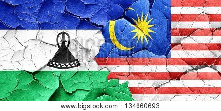 Lesotho flag with Malaysia flag on a grunge cracked wall