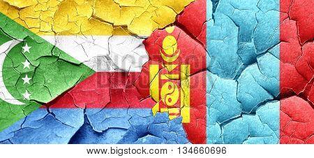 Comoros flag with Mongolia flag on a grunge cracked wall