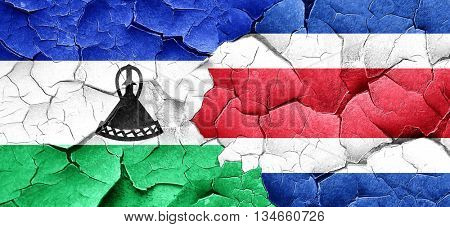 Lesotho flag with Costa Rica flag on a grunge cracked wall