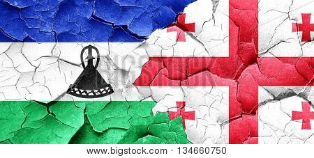 Lesotho flag with Georgia flag on a grunge cracked wall