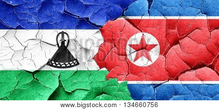Lesotho flag with North Korea flag on a grunge cracked wall