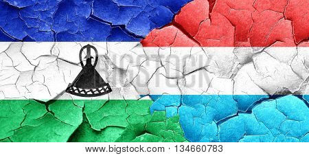 Lesotho flag with Luxembourg flag on a grunge cracked wall