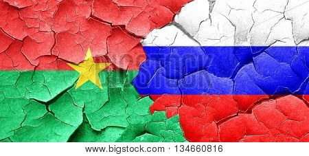 Burkina Faso flag with Russia flag on a grunge cracked wall