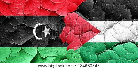 Libya flag with Palestine flag on a grunge cracked wall