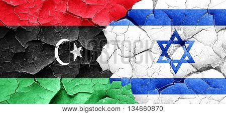 Libya flag with Israel flag on a grunge cracked wall