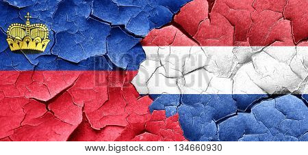 Liechtenstein flag with Netherlands flag on a grunge cracked wal