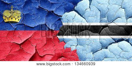 Liechtenstein flag with Botswana flag on a grunge cracked wall