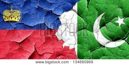 Liechtenstein flag with Pakistan flag on a grunge cracked wall