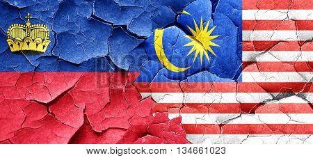 Liechtenstein flag with Malaysia flag on a grunge cracked wall