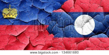 Liechtenstein flag with Laos flag on a grunge cracked wall