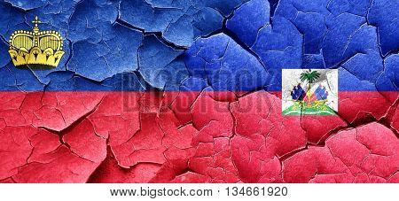 Liechtenstein flag with Haiti flag on a grunge cracked wall