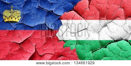 Liechtenstein flag with Hungary flag on a grunge cracked wall
