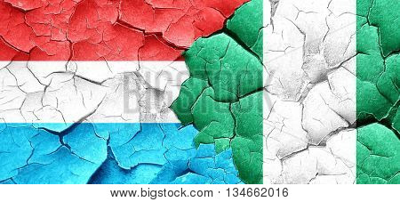 Luxembourg flag with Nigeria flag on a grunge cracked wall