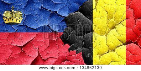 Liechtenstein flag with Belgium flag on a grunge cracked wall