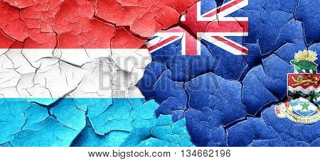Luxembourg flag with Cayman islands flag on a grunge cracked wal
