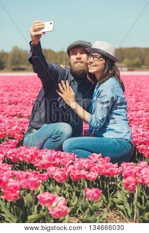Young couple making selfie in a tulip field typical for one of Dutch regions, Noord Holland