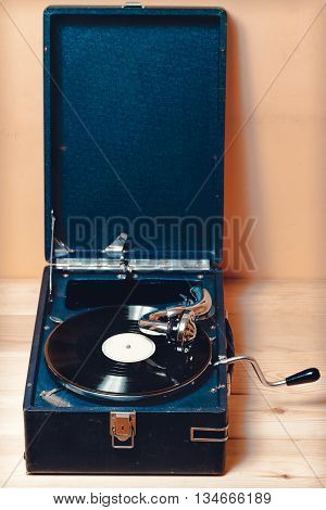 Gramophone with a vinyl record on wooden table. vintage toning